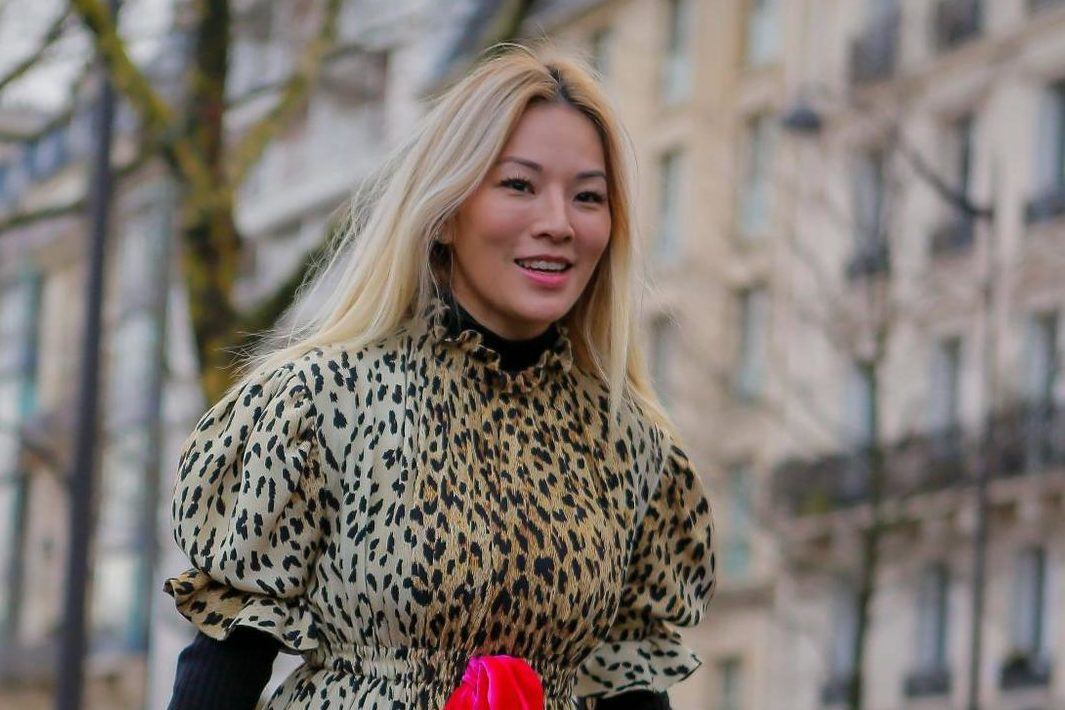 Purple shampoo: Street style photo of an Asian woman with warm blonde hair wearing a leopard print dress with a red tie and red bag
