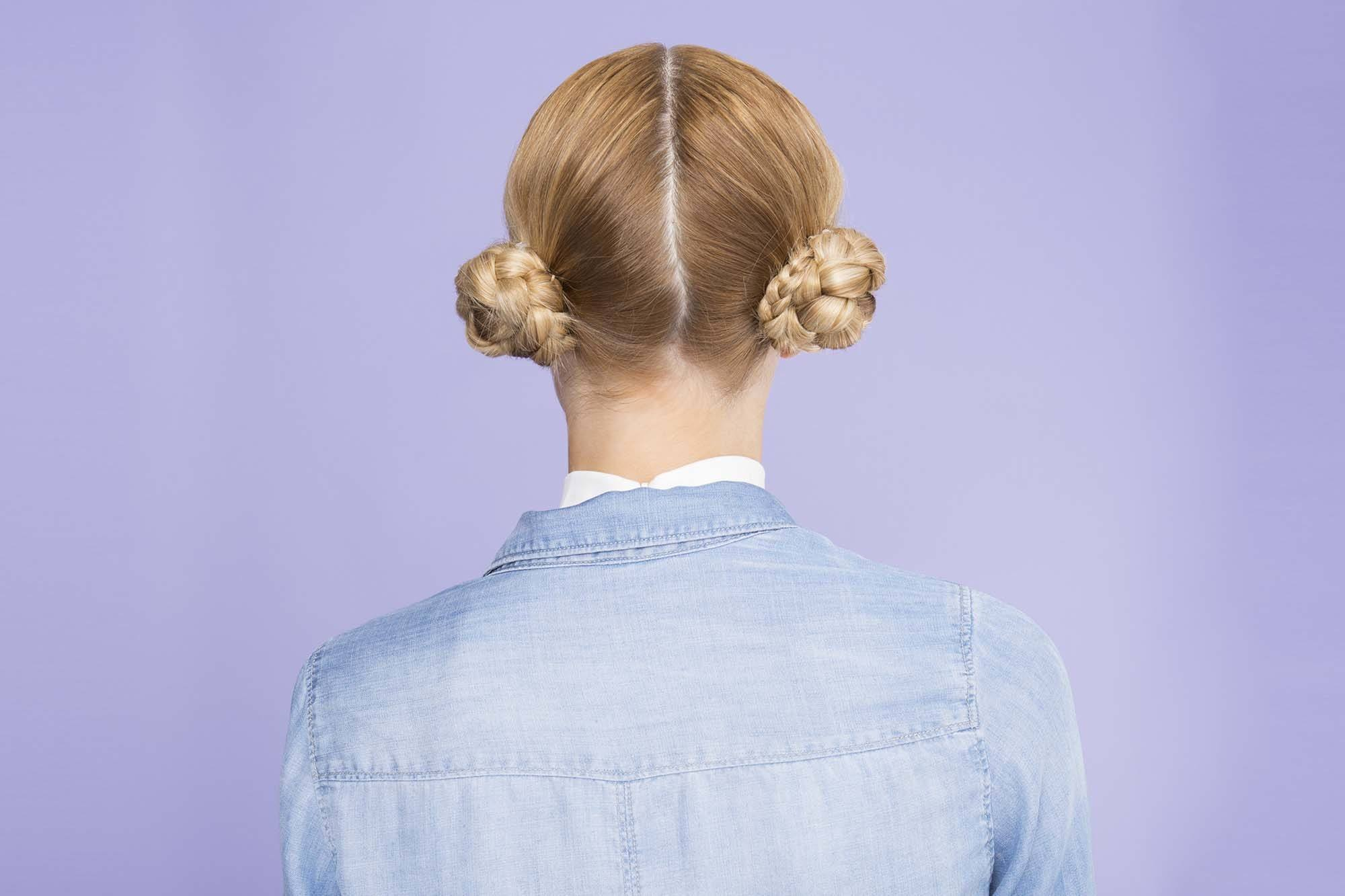 Easy updos - double braided buns on blonde model with blue backdrop