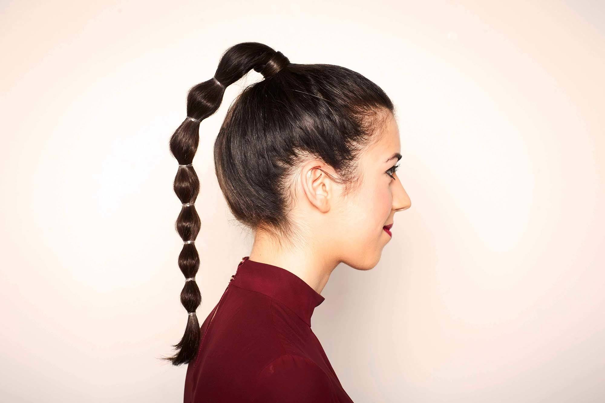 Easy updos - side view of a bubble ponytail on long dark brown hair
