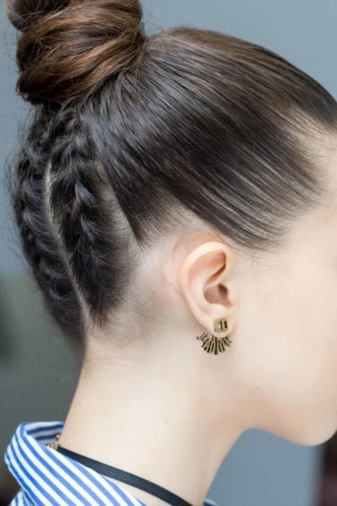 model with dark brunette hair with a braided knot wearing a striped blue shirt wearing dior earrings for the Christian Dior SS17 show