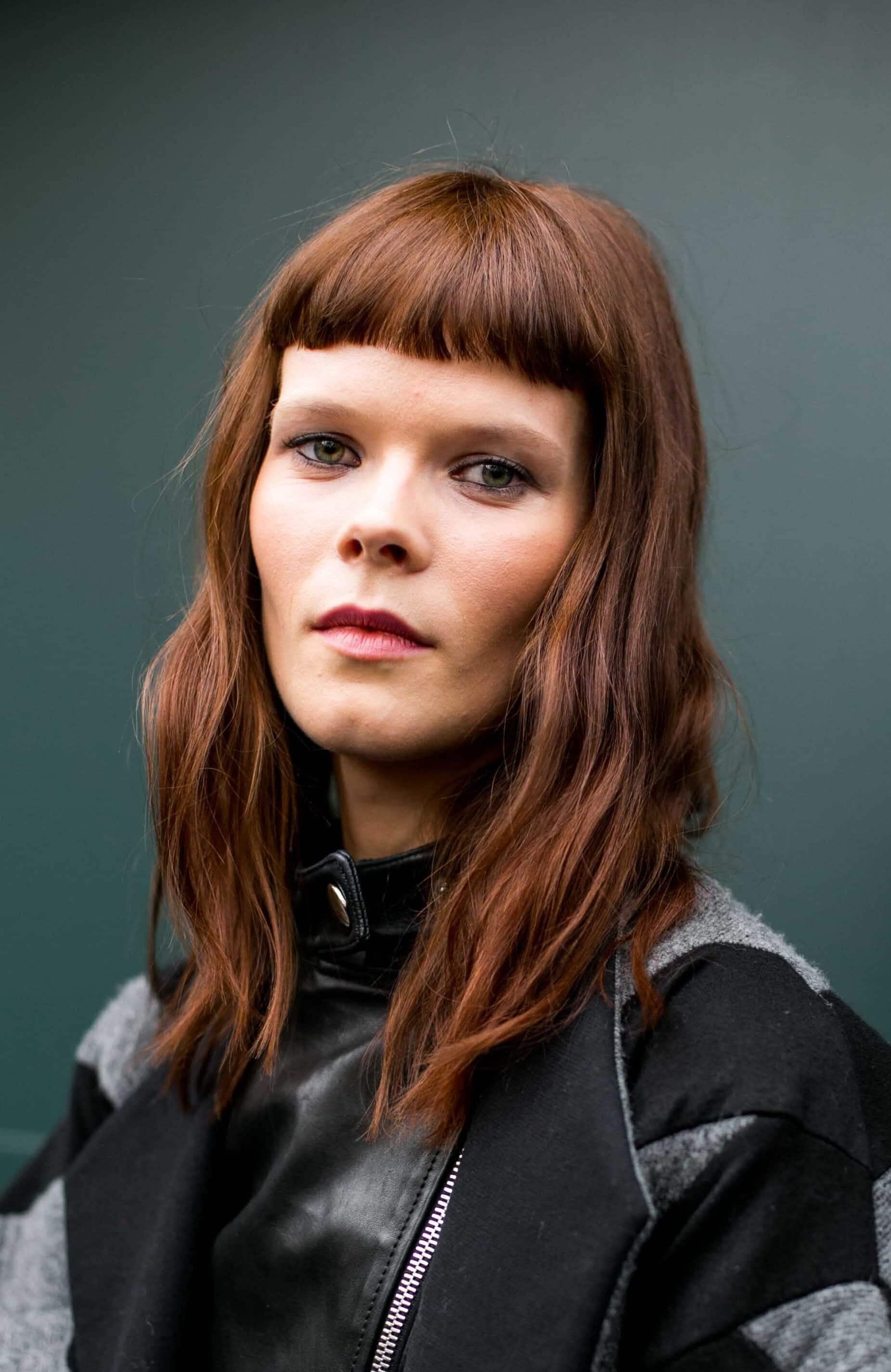 model with copper brown tousled wavy medium-length hair wirth micro fringe