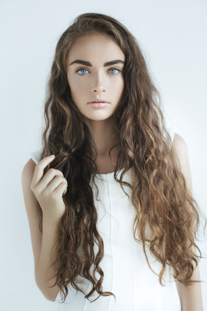 Easy styles for curly hair: A young woman with brown long beachy waves