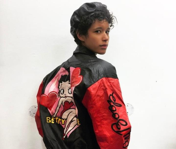 back shot of model with short curly hair wearing beret cap and biker jacket
