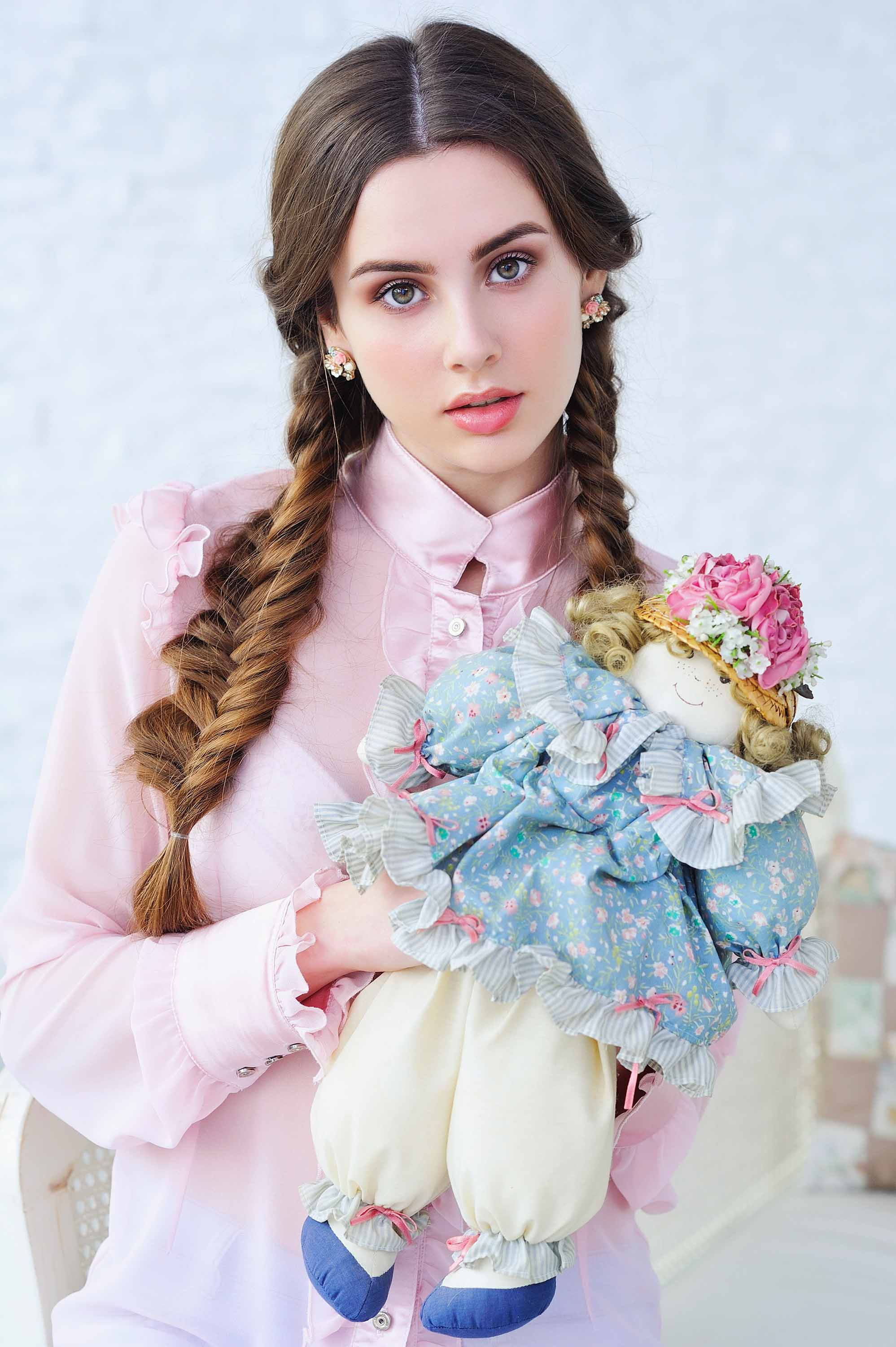 woman with long brown hair in pigtail plaits wearing a pink blouse and holding a doll