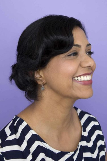 Diwali hairstyles: Woman with dark brown hair in a glamorous wavy updo wearing a stripy top and smiling into the distance