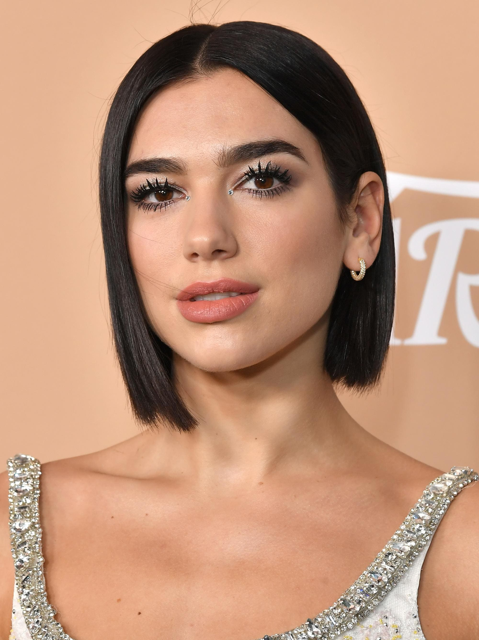 Haircuts for fine hair: Dua Lipa with a blunt dark brown bob, wearing a silver dress on the red carpet