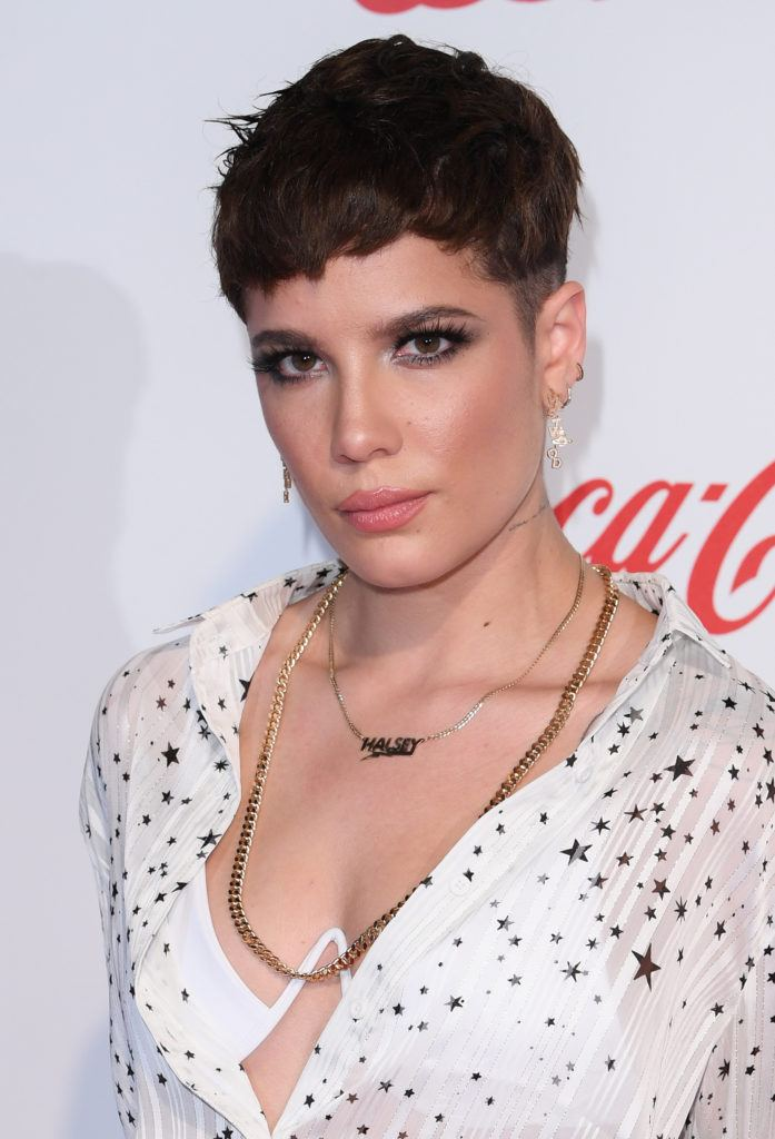 Haircuts for fine hair: Halsey with dark brown choppy pixie with low fade, wearing a white beaded dress with necklaces on the red carpet