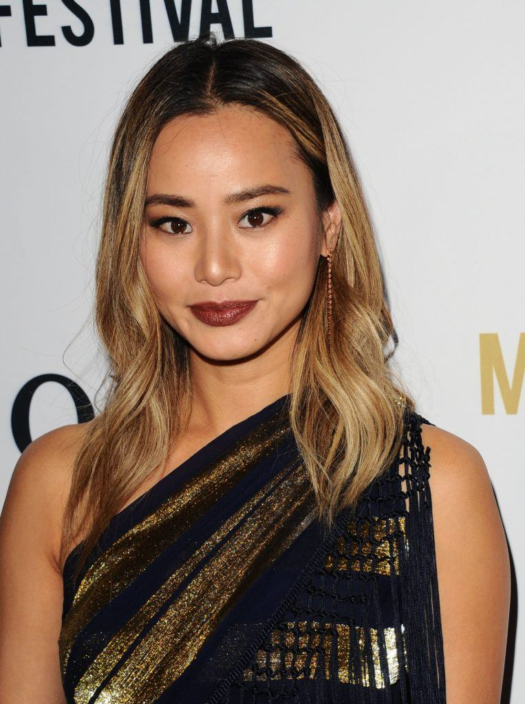 Jamie Chung with mid-length brown to gold ombre hair with soft, volumising layers, wearing all black on the red carpet