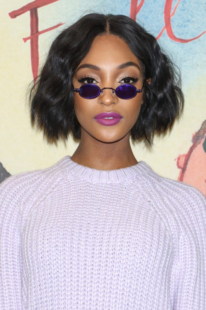 Haircuts for fine wavy hair: Jourdan Dunn with chin-length dark wavy bob, wearing lilac jumper with small glasses on the red carpet