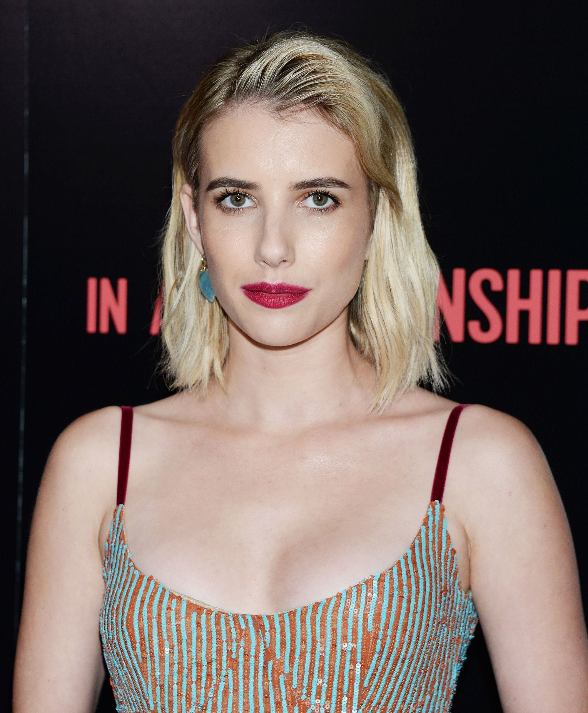 Emma Roberts with platinum blonde textured long bob, styled to the side, wearing glittery dress and red lipstick on the red carpet