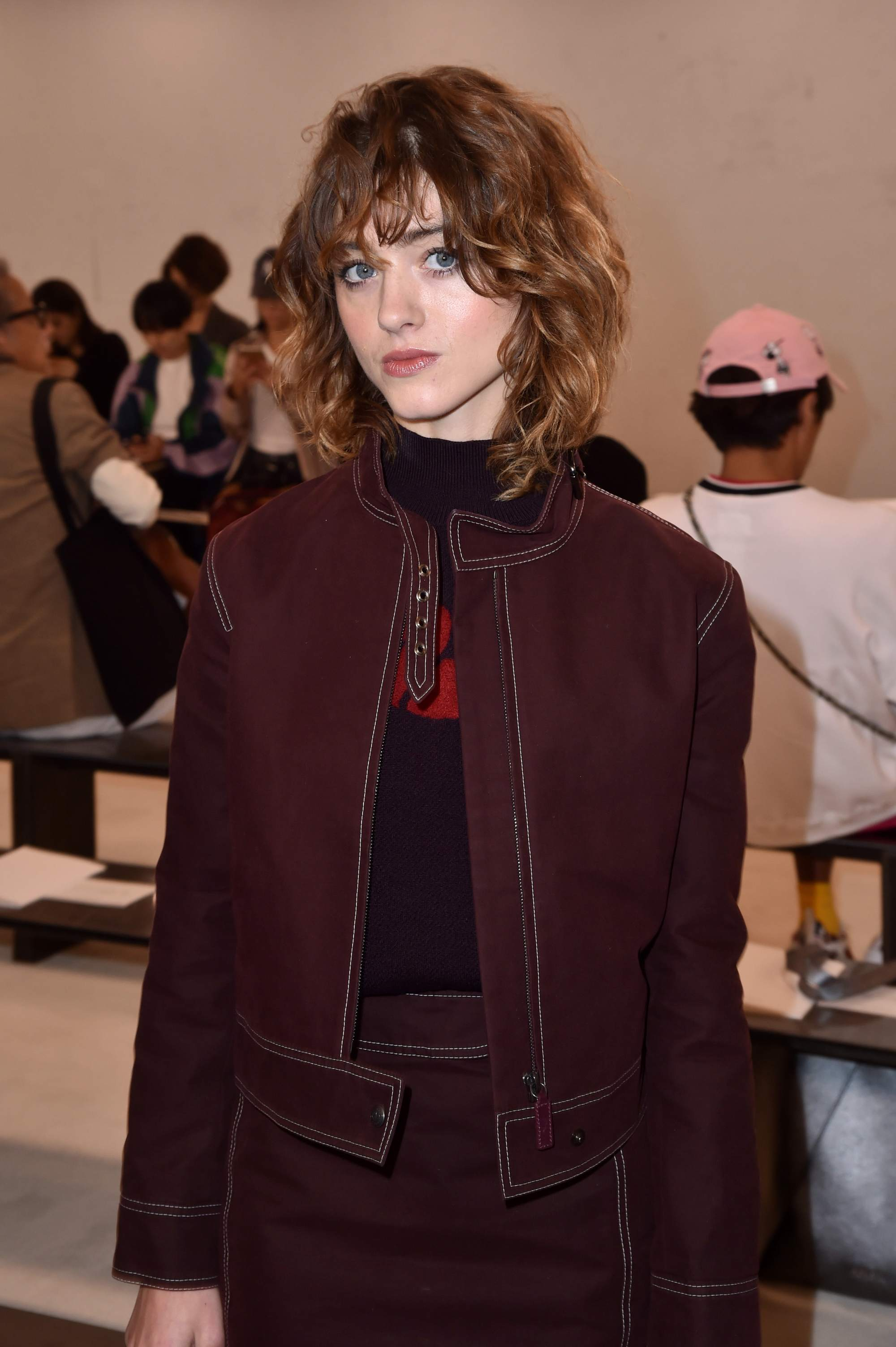 Natalia Dyer with shoulder-length shaggy chestnut brown hair with shaggy fringe, wearing a red denim jacket and skirt