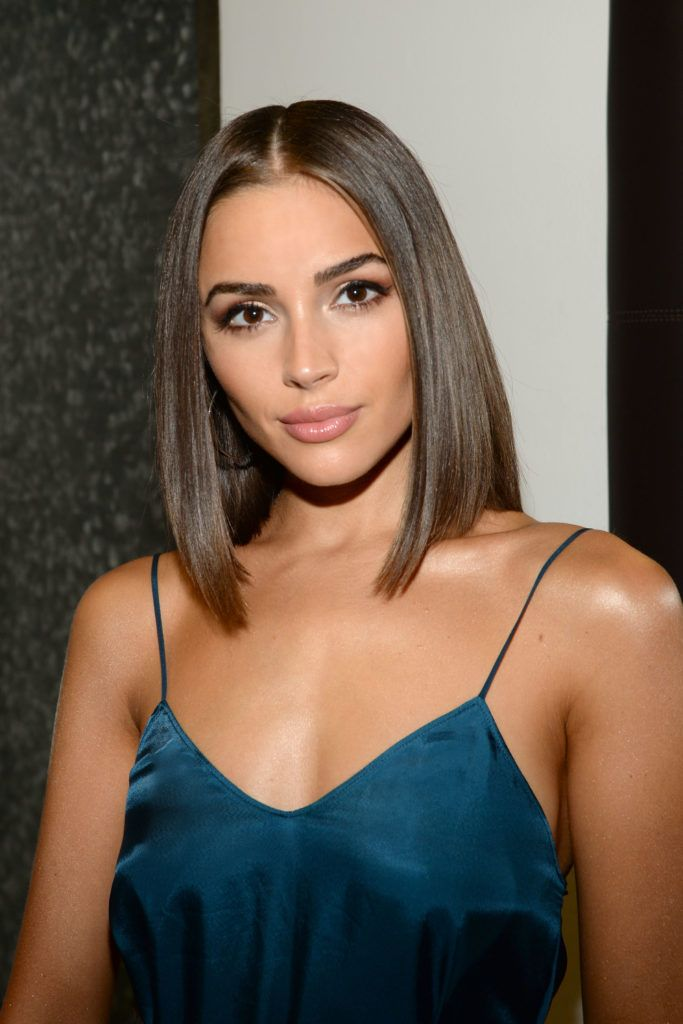Haircuts for fine hair: Olivia Culpo with sleek chestnut blunt A-line haircut, wearing a blue cami top and posing on the red carpet