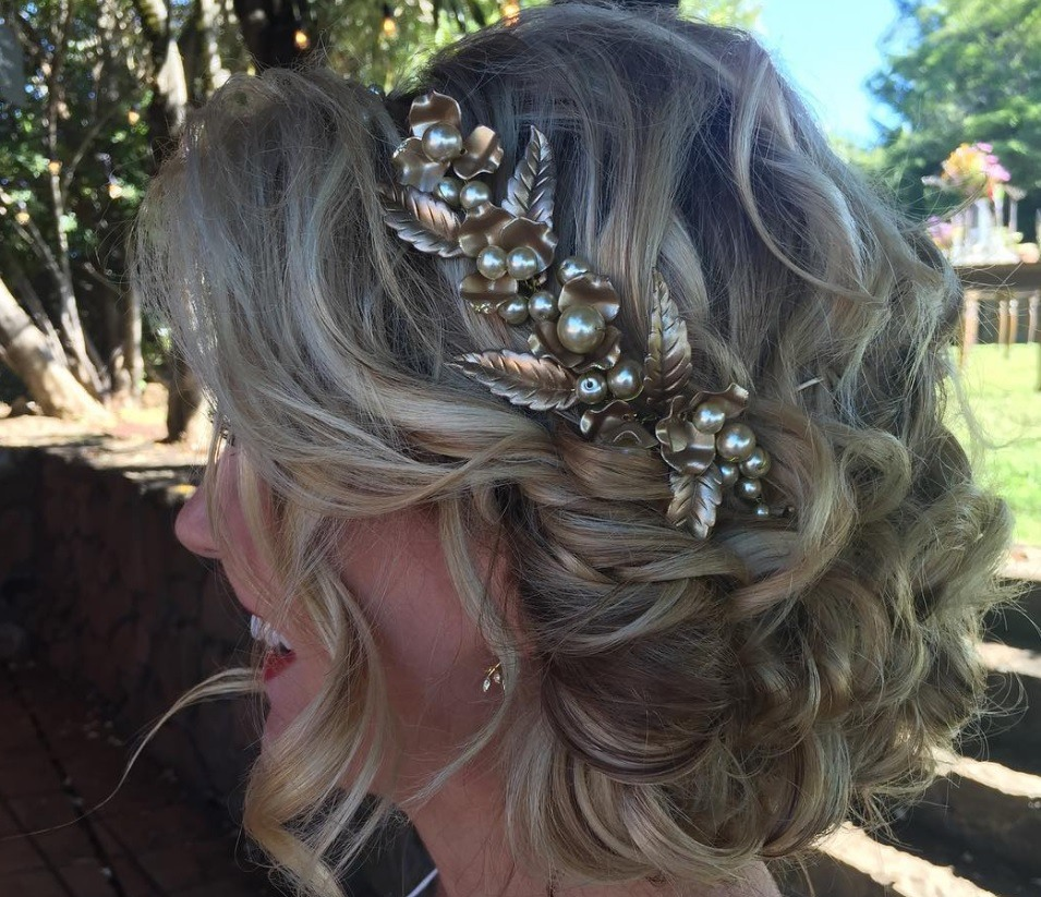 side view of a woman with a curly updo wearing a jewelled headband
