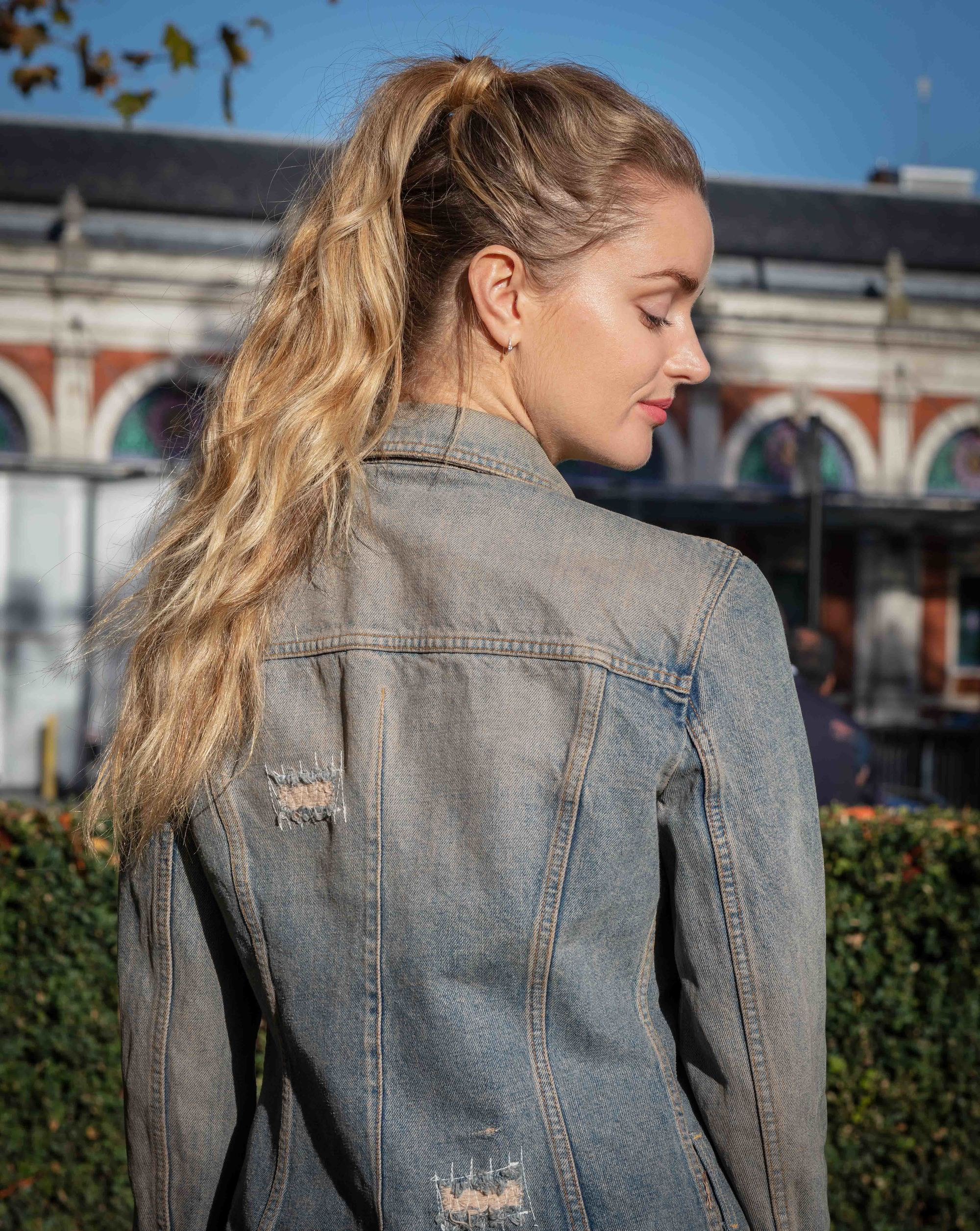 How to style long hair: Outdoor profile shot of a blonde model with long wavy hair in a high double ponytail, wearing a denim jacket