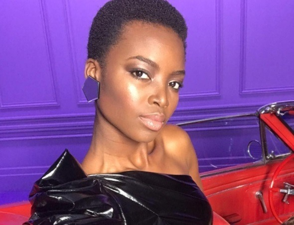 close up shot of maria borges with short afro hairstyle, wearing black dress