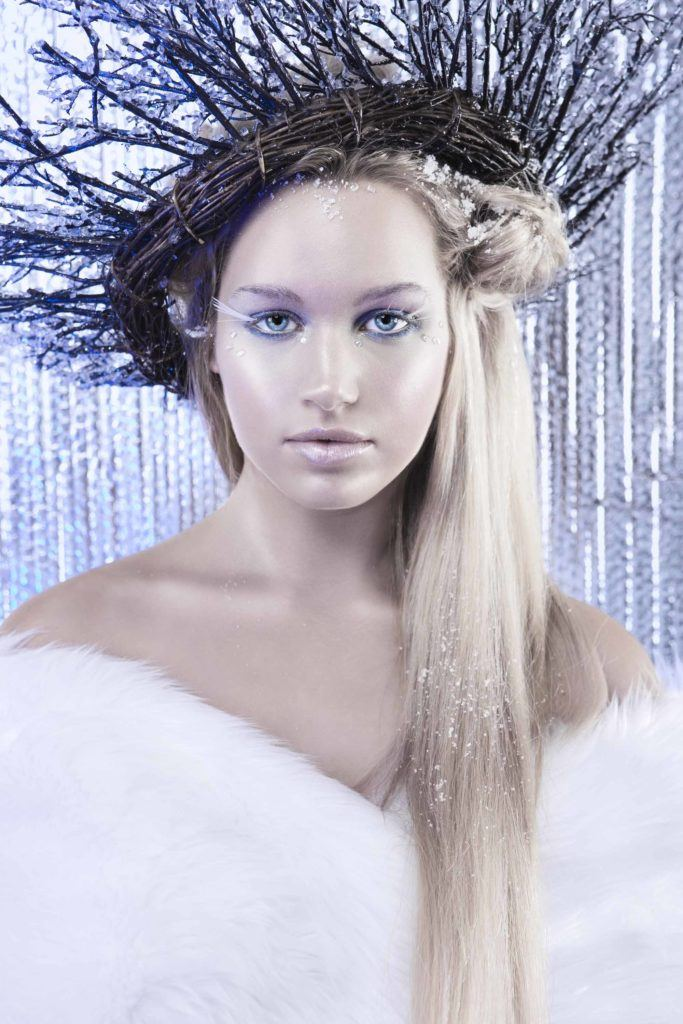 woman dressed as an ice queen with long blonde hair wearing white fur and twigs in