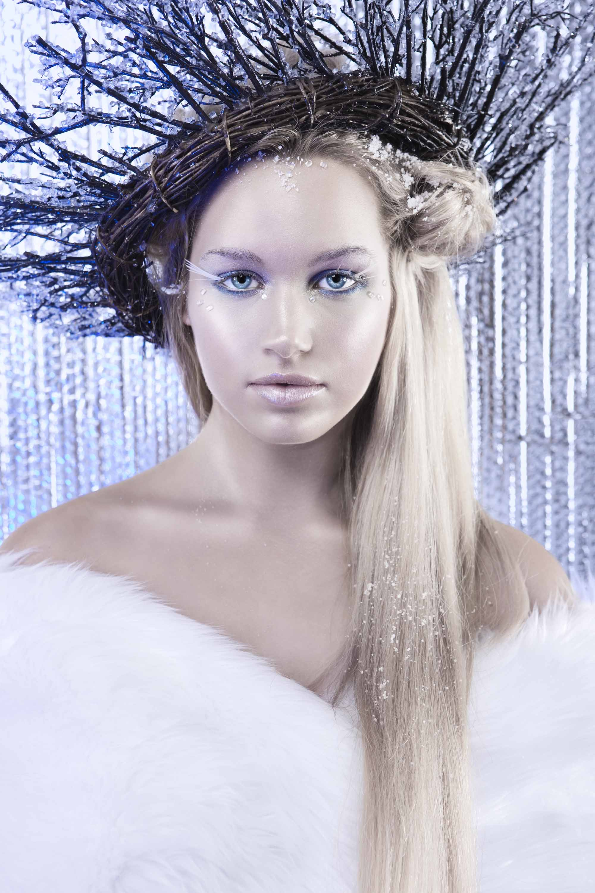 woman dressed as an ice queen with long blonde hair wearing white fur and twigs in her hair
