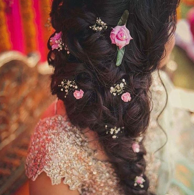 Indian wedding hairstyles: close up shot of woman with dark brown hair styled into an intricate side braid, with flowers woven into it