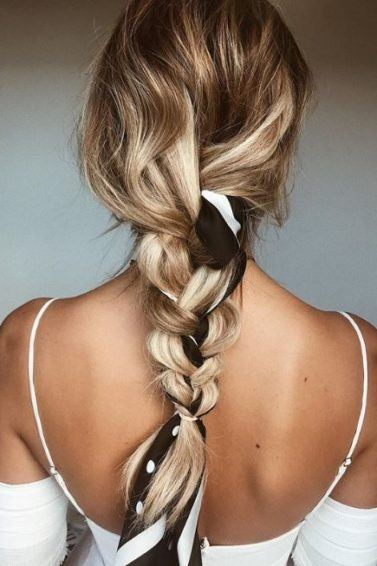 hairstyles for thick wavy hair: back view of a single braid woven with a headscarf on wavy blonde long hair