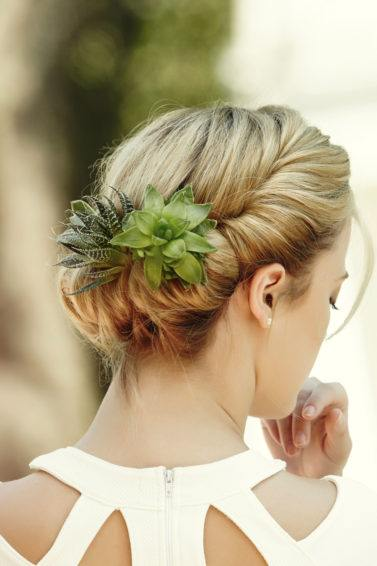 back view of a blonde model wearing a white cut out dress with her hair in a gibson tuck with succulents clipped into it