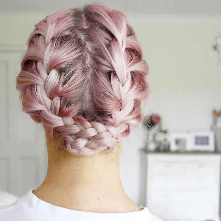 French plait styles: Woman with pink hair and a reverse milkmaid braid