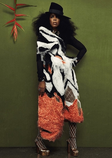 Kelly Rowland for Schon magazine photoshoot with natural hair and a hat weaering a black and white and orange outfit