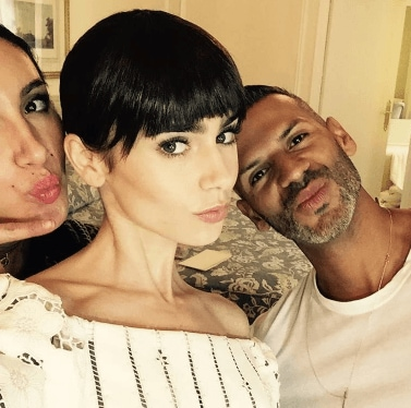 selfie of Lilly Collins with her two friends posing with her dark hair cut into a blunt fringe and the guy with a short cut and facial stubble