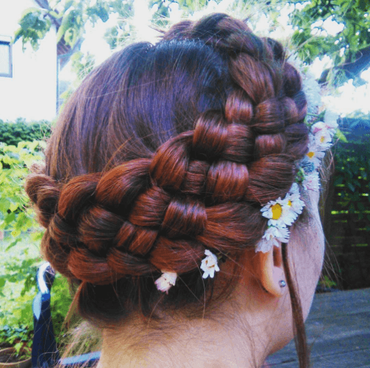 Medieval hairstyles: Back view of a woman's red hair in a braided halo updo