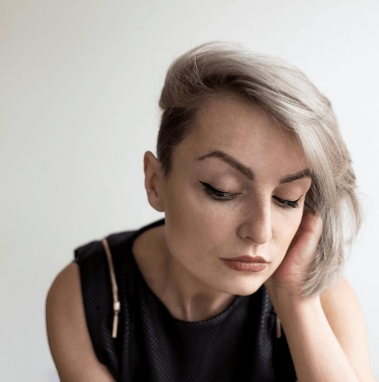 shot of a woman with grey blonde short hair worn to the side with an undercut wearing a balck top