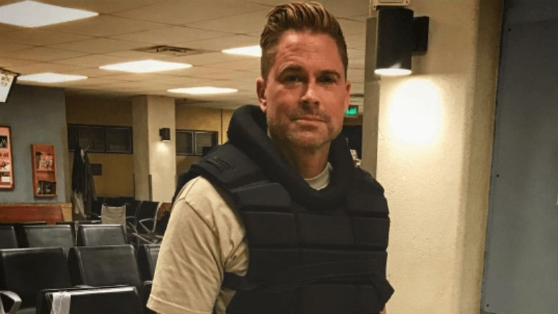 Rob Lowe on set filming wearing a black bullet proof vest and khaki trousers with his hair styled into a quiff