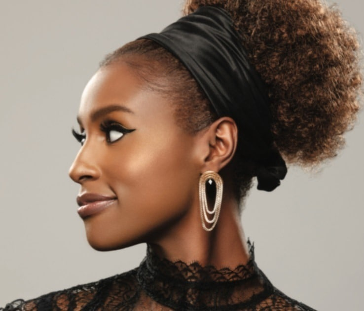 close up shot of issa rae with a curly ponytail with a headband silk scarf on, wearing earrings and posing