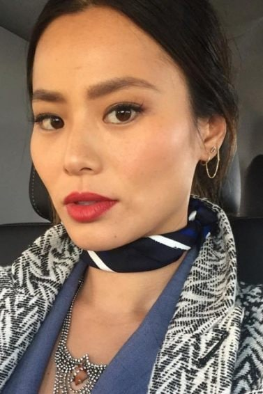 Jamie Chung selfie wearing a black and white coat zig-zag coat and a neck scarf with dark brown hair worn in an updo