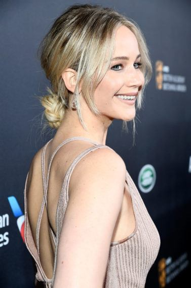 Jennifer Lawrence on the red carpet wearing a strapy back dress with a low bun updo in a light blonde colour