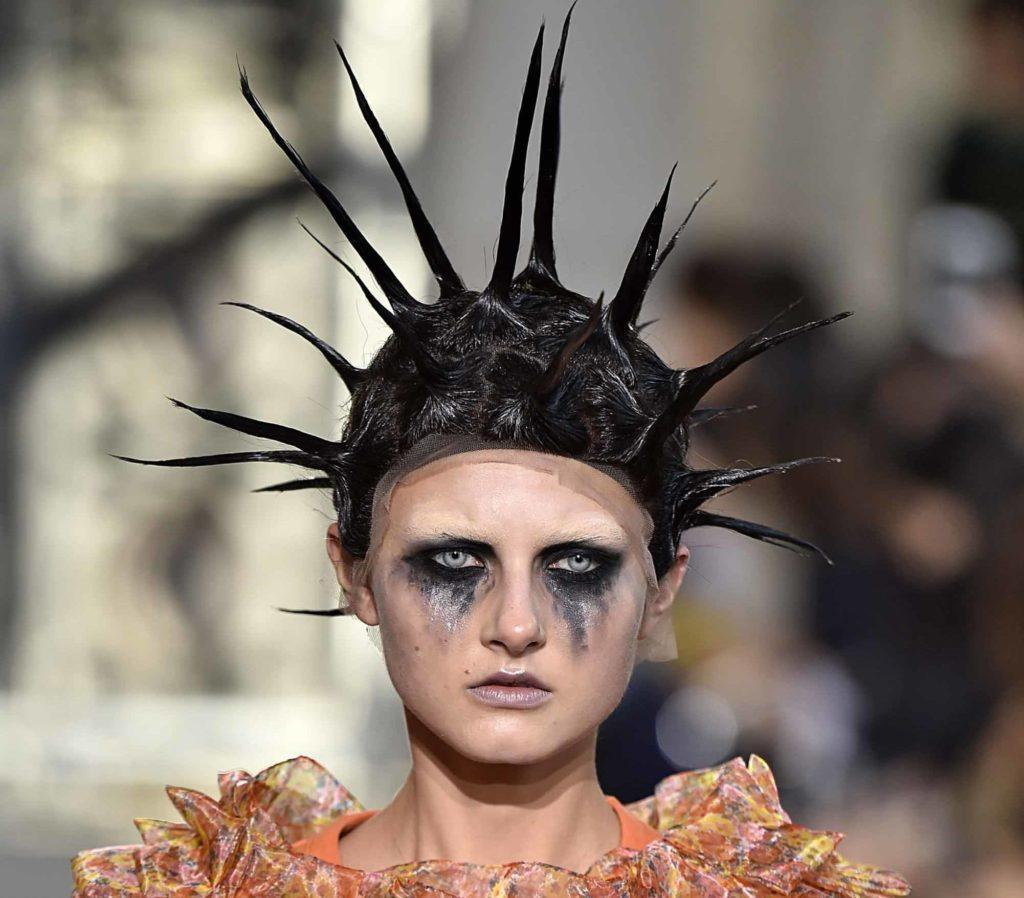 runway model with dark hair in long spikes and smudged make up