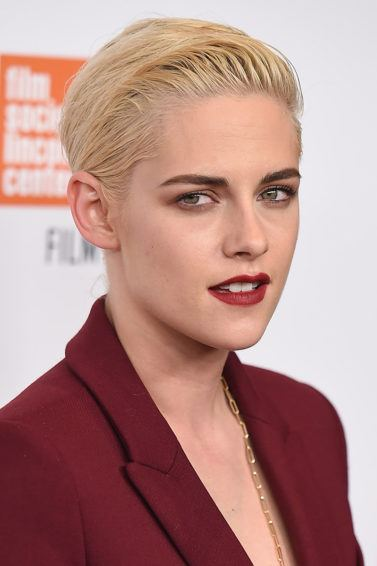 Kristen Stewart on the red carpet wearing a deep red blazer with bleached blonde hair cut into a short pixie and styled into a wet look