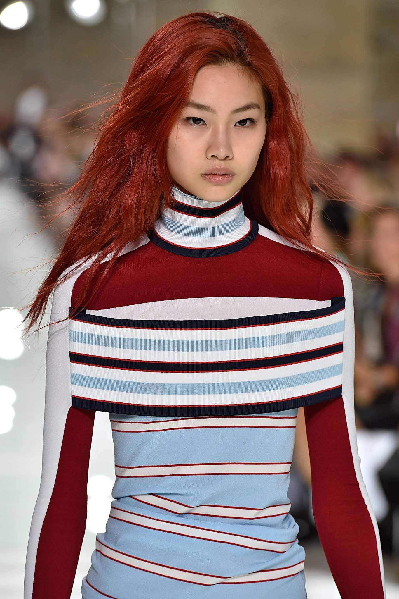 Model on runway with long tousled red hair wearing a striped outfit at Louis Vuitton SS18.