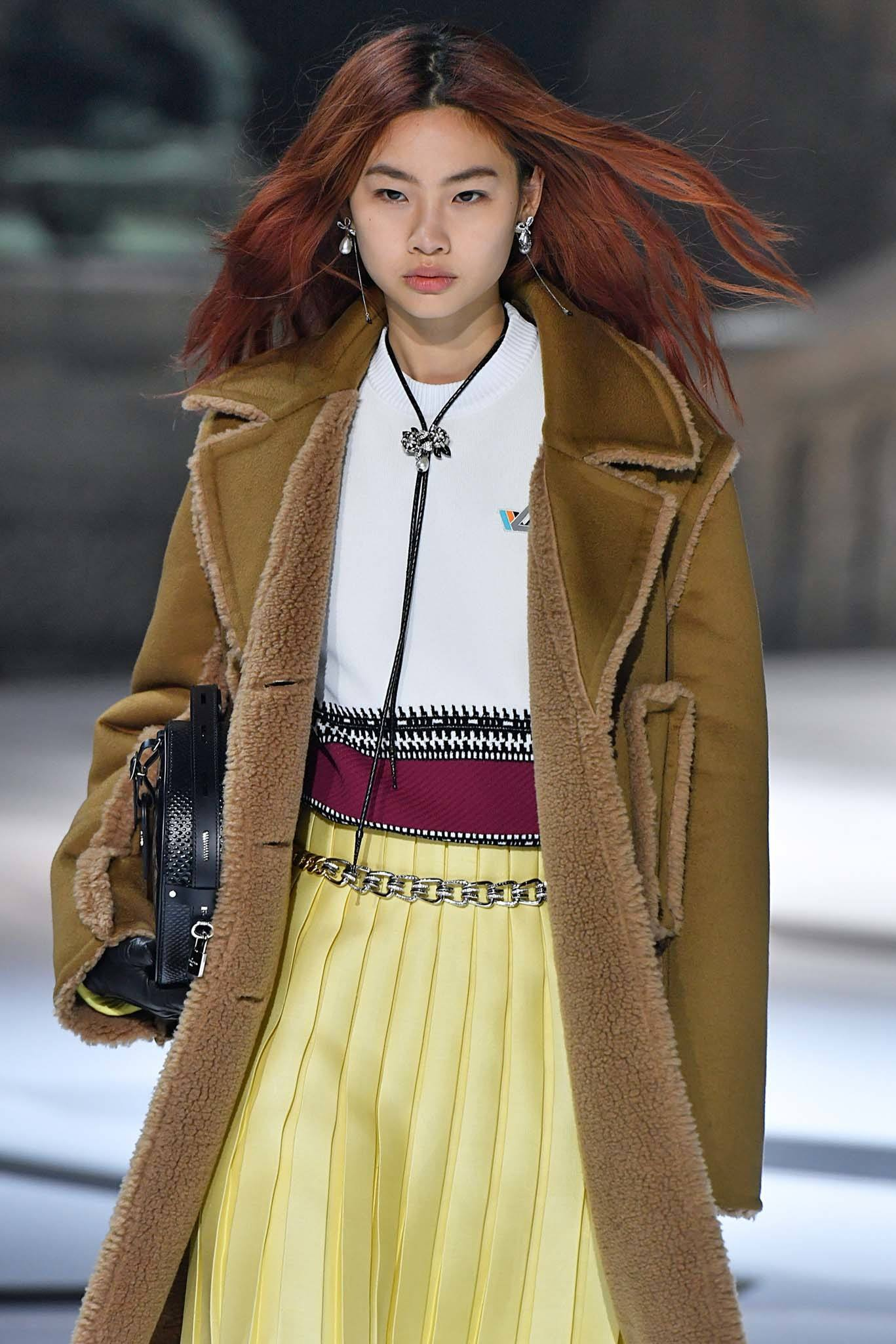 Woman on runway with long red hair wearing a yellow skirt and brown teddy coat at Louis Vuitton FW18 show.