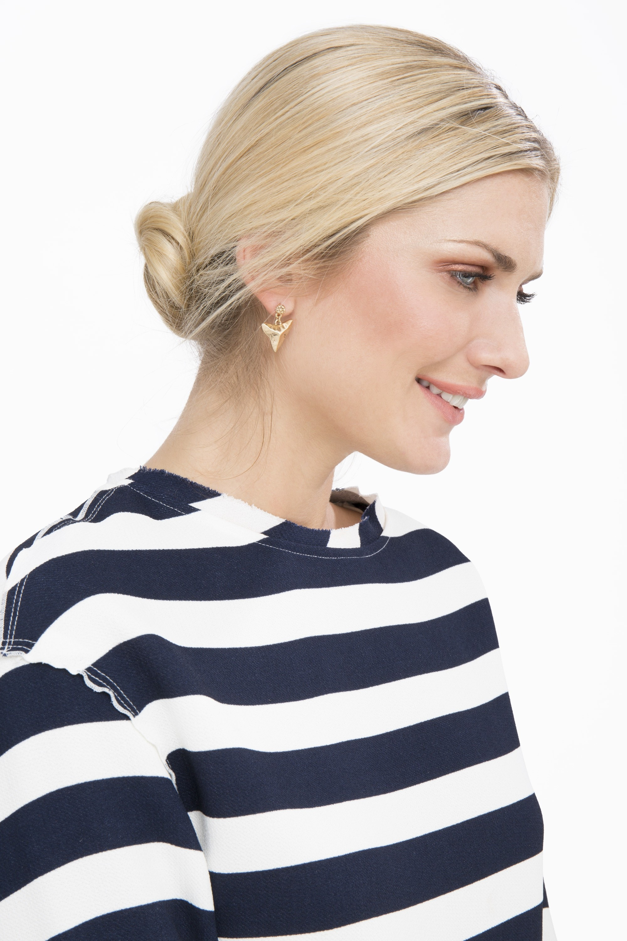 model wearing a striped top and a low bun in her blonde hair