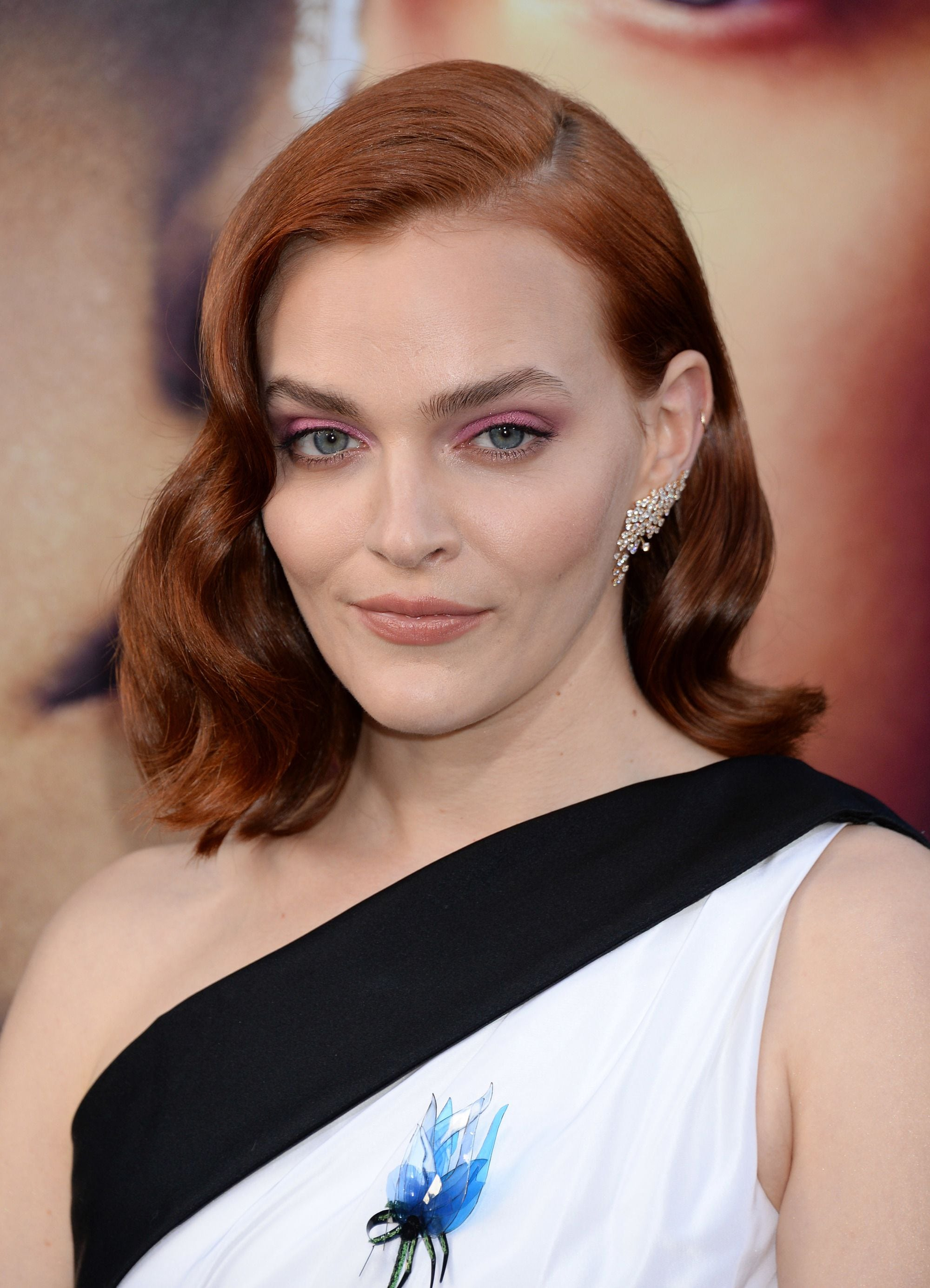 Madeline Brewer with red shoulder length hair with Hollywood waves wearing a off the shoulder dress.