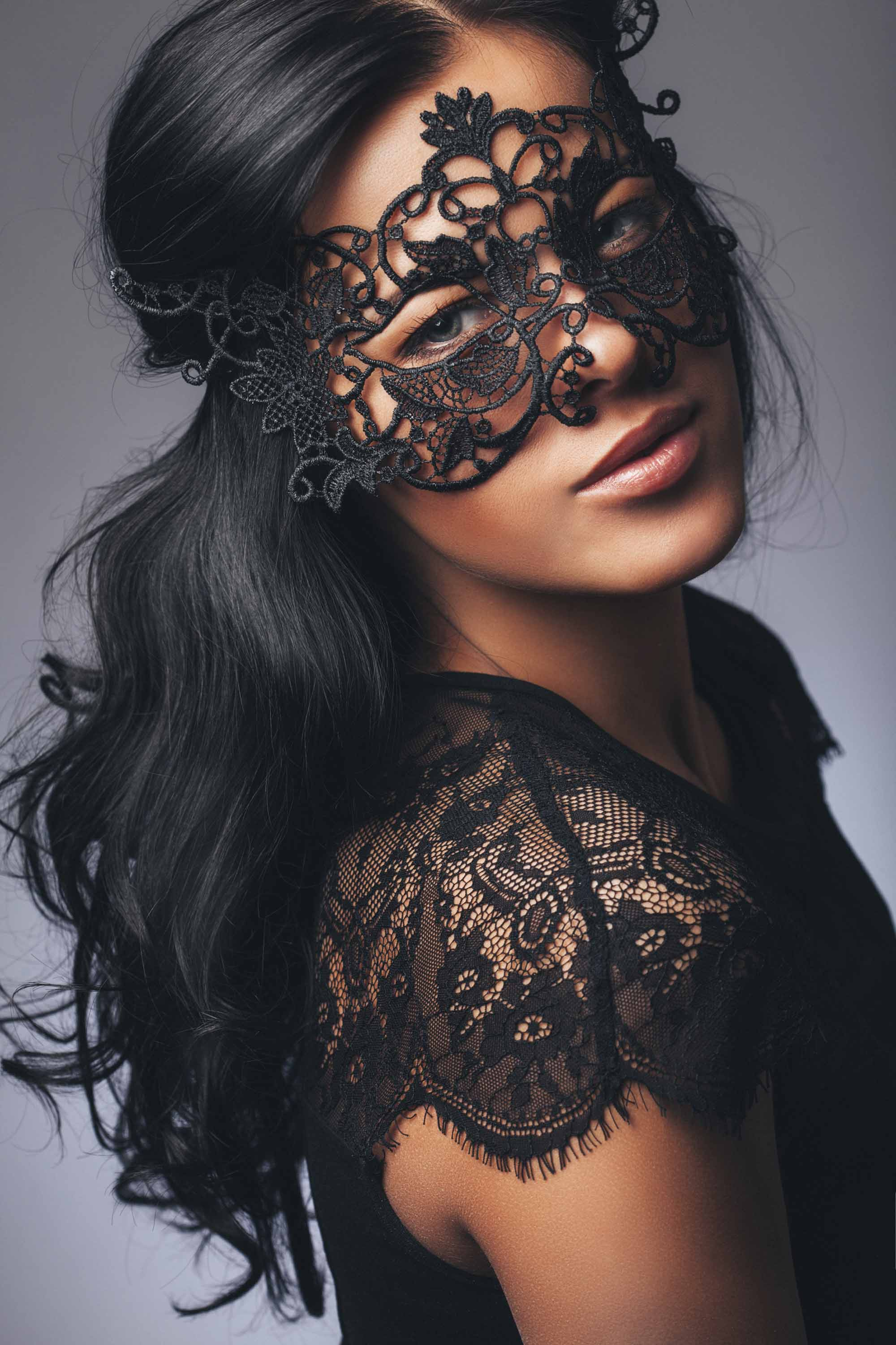 woman with long dark hair in waves wearing a masquerade mask and black lace top