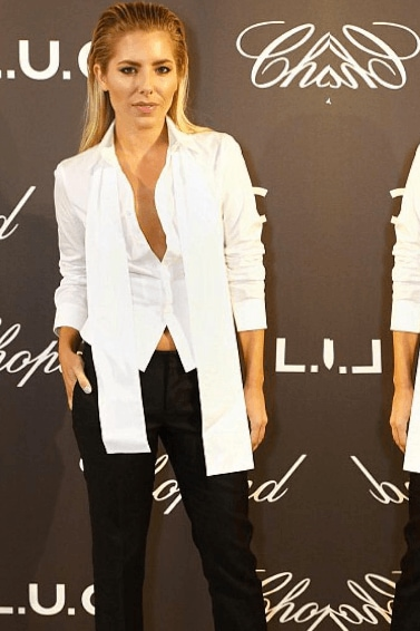 Mollie King on the red carpet wearing a white blazer and black trousers with her hair blonde hair slicked back in a wet look