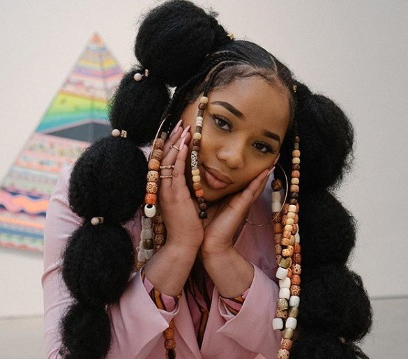 Black history month hair: Close up shot of a woman with long afro bubble pigtails, decorated with beads, wearing pink and posing in a studio setting