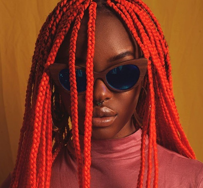 Black history month hair: Close up shot of a woman with long orange red box braids, wearing sunglasses with rosy mauve pink top, posing in a studio