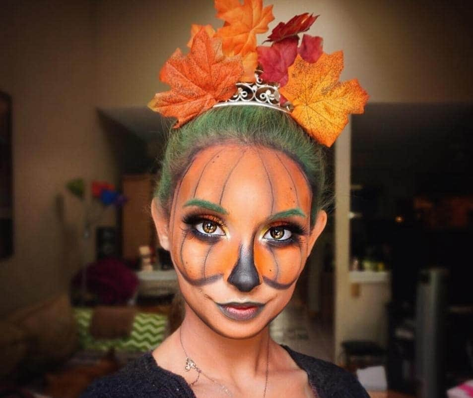 woman with pumpkin face paint and green hair with autumnal leaves