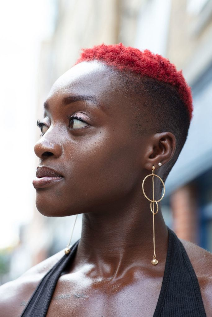 Black history month hair: Close up shot of a woman with red TWA with a shaved undercut, wearing earrings, posing for a street style shot