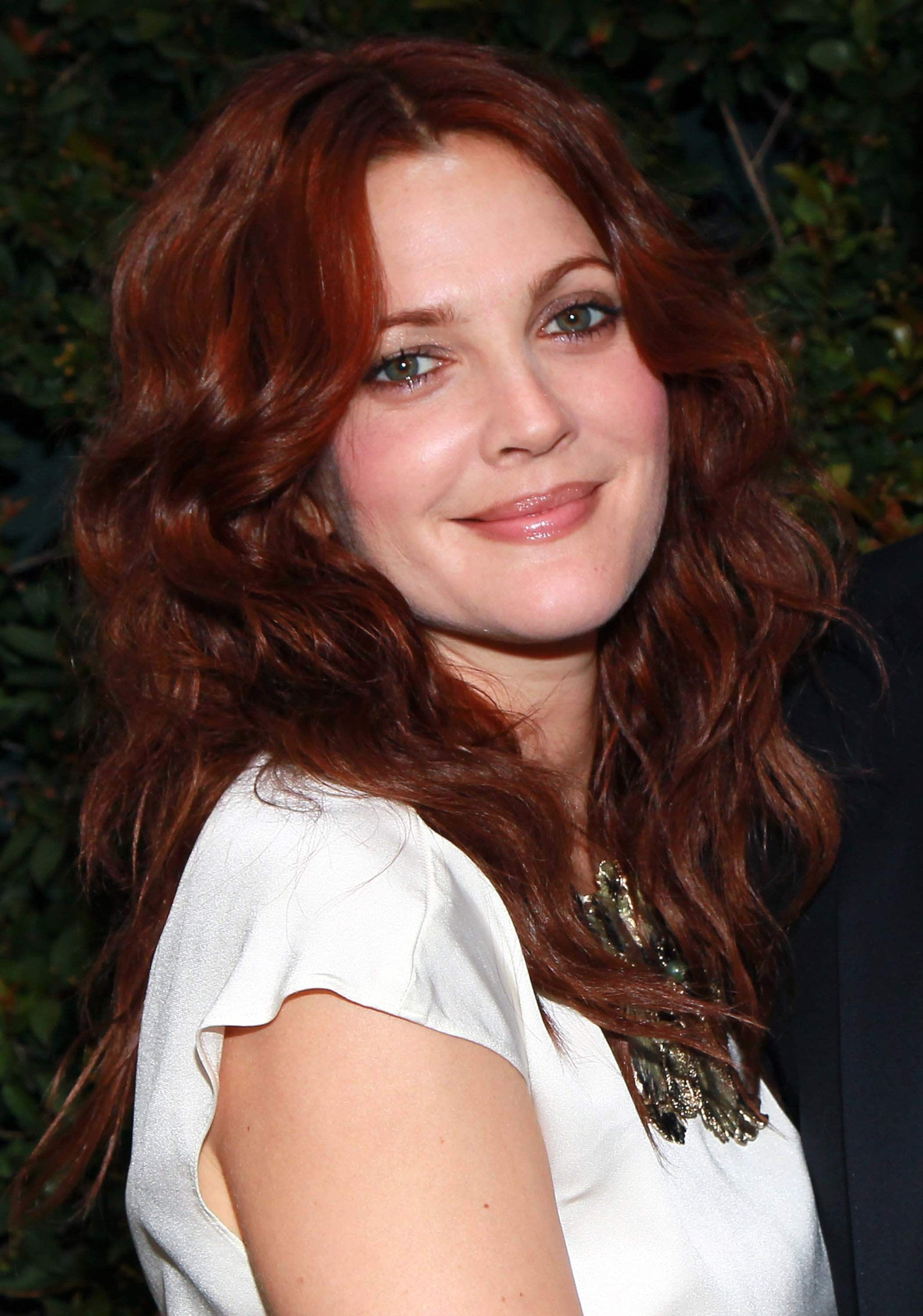 drew barrymore with long dark red hair in a curly finish wearing white t-shirt
