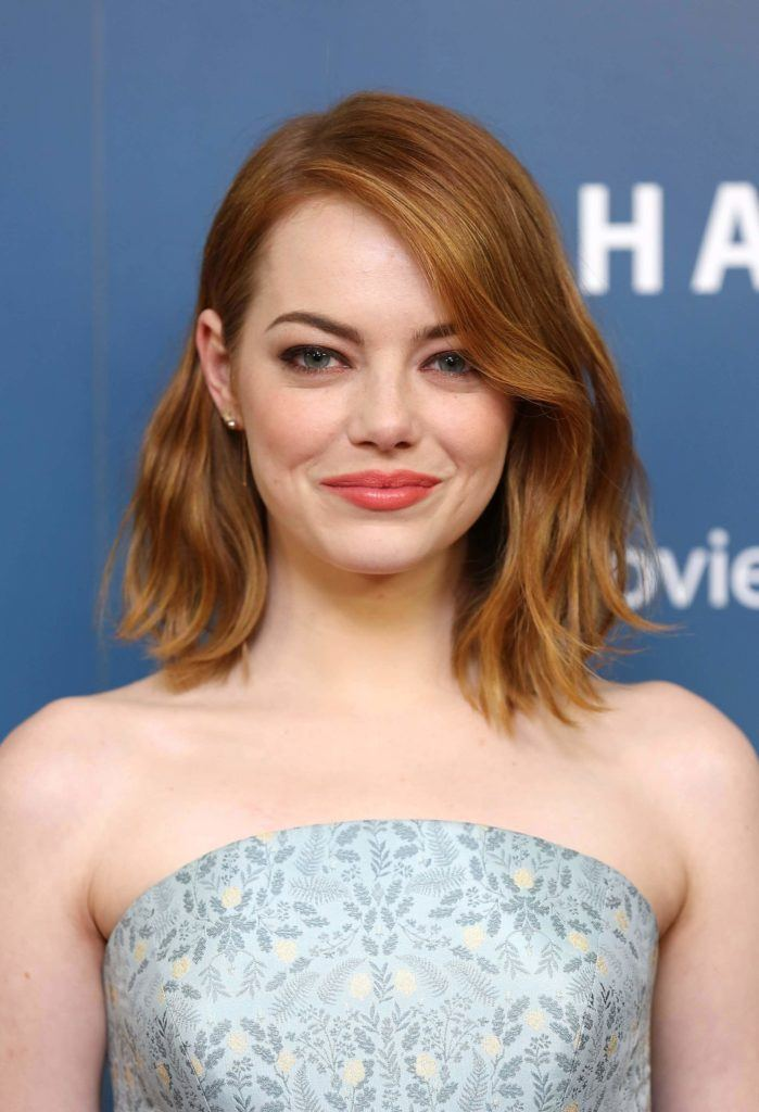 emma stone at red carpet event with long bob wavy ginger red hair styled in side-parting with one side of hair tucked behind her ear wearing strapless blue grey pattern dress
