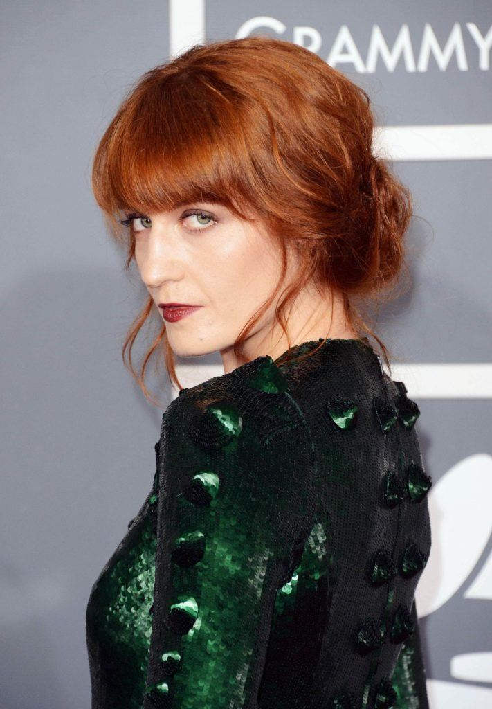 florence welch with bright copper red hair at grammy awards styled in a low updo with full fringe wearing green dress
