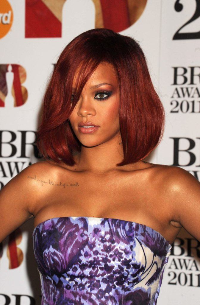rihanna at brit awards with bob-length deep red hair in side parting swept fringe wearing strapless purple dress