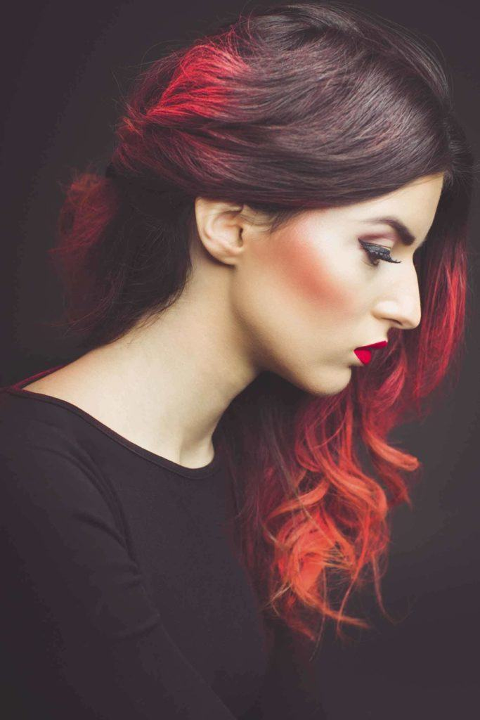 side view of woman with dark brown long wavy hair with red ombre finish